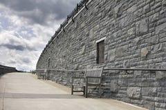 Bancos a lo largo de la pared de piedra de parques públicos foto de archivo libre de regalías