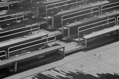 Bancos vazios na tribuna com fundo preto e branco da cena imagens de stock