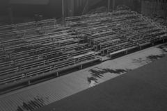 Bancos vazios na tribuna com fundo preto e branco da cena imagens de stock royalty free