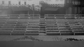 Bancos vazios na tribuna com fundo preto e branco da cena foto de stock