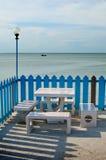 Bancos y lámpara de mármol por el mar Imagen de archivo