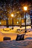 Bancos y lámparas en la noche del invierno Fotos de archivo