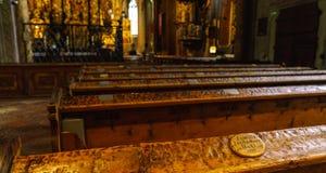 Bancs antiques à l'intérieur de la cathédrale catholique avec u Photographie stock libre de droits
