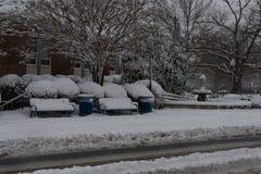 Bancs couverts dans la neige devant le bâtiment photos libres de droits