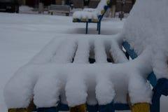 Bancs dans la cour couverte de neige Images libres de droits