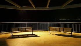 Bancs de stationnement la nuit Photo stock
