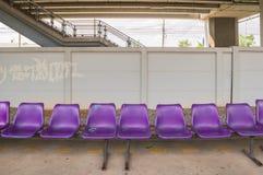 Bancs pourpres de plastique dans la gare ferroviaire Image libre de droits