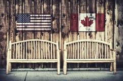 Bancs rustiques de rondin avec les Etats-Unis et le drapeau de Canada photo libre de droits
