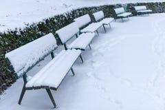 Bancs sous la neige en parc public en hiver images libres de droits