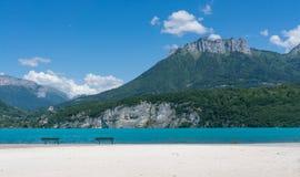 Bancs sur le sable blanc pur devant le d& x27 de laque ; Annecy Photographie stock libre de droits