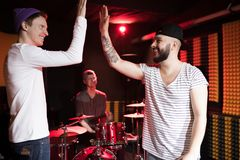 Band Buddies. Side view portrait of tattooed modern singer high fiving friend while rehearsing in dim recording studio Royalty Free Stock Photography