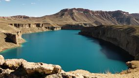 Natural dams on  lake basin with snow covered mountains. Band-e Amir Lakes. Band-e Amir National Park, Bamyan Province, Afghanistan. Pan Right. Landscape stock footage
