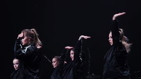 Dynamic cute girls in black sportive black clothes dance on stage at festival. Band of energetic nice-looking girls wearing black sport clothes synchronically stock video