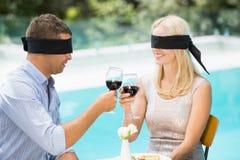 Band för ögonen på par som rostar rött vin medan Arkivbilder