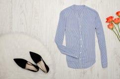 Band för blus in fine, skor och orange rosor på en träbackg Arkivfoton
