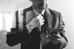 band för framgångaffärsmaninnehav och använda smart telefon som tänker, f arkivfoto