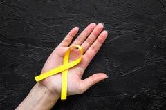 Band för handhållguling för självmord- och endometriosismedvetenhet på svart copyspace för bästa sikt för bakgrund Arkivbild