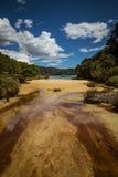 Band för sandig strand och havunder en blå himmel med vita moln, Fotografering för Bildbyråer