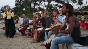 Band het spelen op djembe op een zandig strand stock video