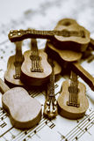 Band of live acoustic guitars. Creative musical artwork on a group of toy music instruments on melody song chart. Band of live acoustic guitars Stock Photos