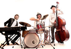 Band playing. Band made up of men who playing double bass, piano and drums Royalty Free Stock Image