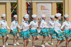 Band majorettes perform various dancing skills on city park Stock Photos