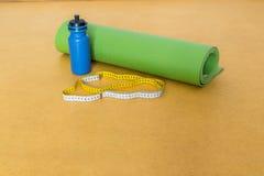 Band, matt yoga och flaska för cm av vatten för övning på gul bakgrund Arkivbild