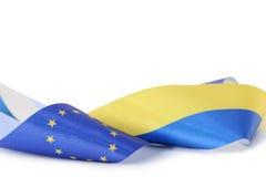 Band med ukrainska och europeiska fackliga flaggor som isoleras på vit Royaltyfria Bilder