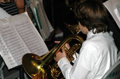 Band member. Middle school advanced band member playing Mellophone (similar to French Horn) from sheet music at X-mas performance Royalty Free Stock Photo