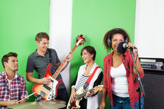 Band Members Performing In Recording Studio. Happy male and female band members performing in recording studio Stock Photography