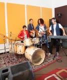 Band Members Performing In Recording Studio. Male and female band members performing in recording studio Royalty Free Stock Image