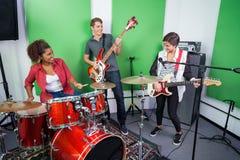Band Members Performing In Recording Studio. Multiethnic male and female band members performing in recording studio Royalty Free Stock Photo