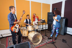 Band Members Practicing In Recording Studio. Male and female band members practicing in recording studio Royalty Free Stock Images