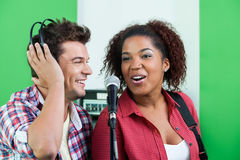 Band Members Singing In Recording Studio. Excited band members singing in recording studio Stock Photos
