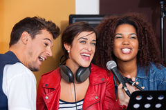 Band Members Singing In Recording Studio. Happy male and female band members singing in recording studio Stock Image