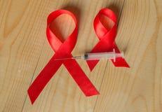 Band och injektionsspruta för medvetenhet rött på träbakgrund: världsdag av kampen mot HJÄLPMEDEL, befordransamhällsstöd för Royaltyfri Bild