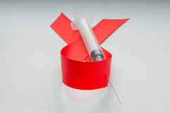 Band och injektionsspruta för medvetenhet rött på vit bakgrund: världsdag mot HJÄLPMEDEL, befordran av samhällsstöd för Fotografering för Bildbyråer