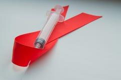 Band och injektionsspruta för medvetenhet rött på vit bakgrund: världsdag mot HJÄLPMEDEL, befordran av samhällsstöd för Arkivfoton