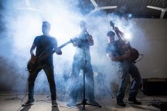 Band performing live on a stage. Rock and roll band members performing live on stage with lights and smoke Stock Images