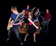 Band Practice. Six teens in a high school rock band practicing on a stage Stock Photo