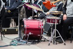 A band preparing to perform in the street at summer open-air. Maroon drum set, red guitar, mic, other musical equipment. royalty free stock image