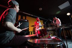 Band Recording Music in Studio. Group of young musicians performing in dim recording studio making new album, drummer in foreground, copy space Royalty Free Stock Images