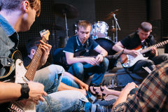 Band rehearsal before a live performance. Guitarists of music group sitting with their instruments and strum the guitar royalty free stock photo