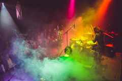 Band on stage with fog and colored lights Royalty Free Stock Images