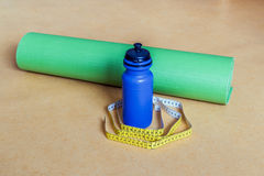 Band, yoga är matt, och flaska för cm som av vatten på idrottshallen Royaltyfri Fotografi