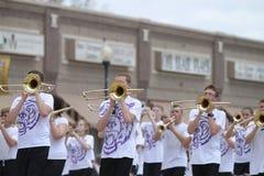 Banda adolescente que juega los trombones en un desfile de la pequeña ciudad en América Imágenes de archivo libres de regalías