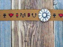 Banda d'annata con gli ornamenti ricamati ed il vecchio fiore del bottone Fotografie Stock