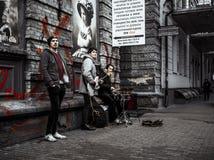 Banda de la música de tres hombres que juega y que canta en la calle imagen de archivo