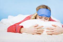 Banda del ojo el dormir de la mujer que lleva joven en cama Foto de archivo libre de regalías