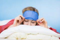 Banda del ojo el dormir de la mujer que lleva joven en cama Imagenes de archivo
